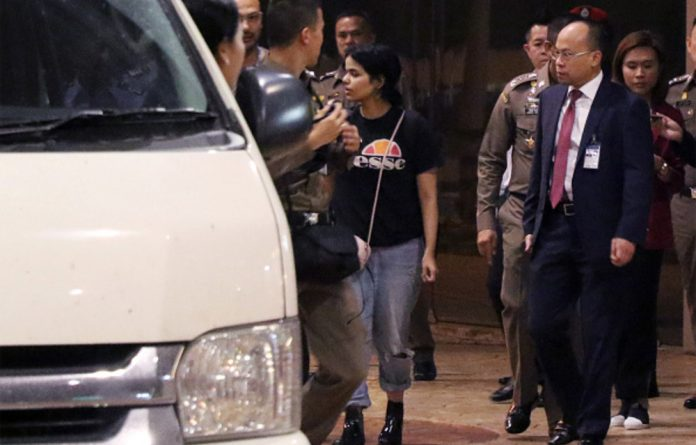 Rahaf Mohammed al-Qanun is escorted to a vehicle by a Thai immigration officer and United Nations High Commissioner for Refugees