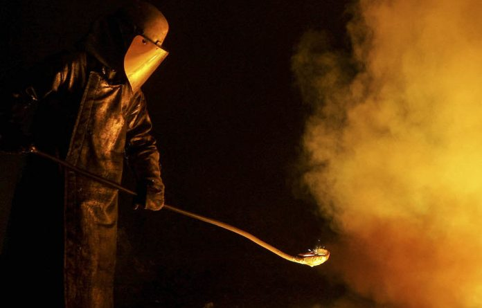 A worker at an Arcelor steel plant works at a furnace in Florange-Hayange near Metz in the French Lorraine region.