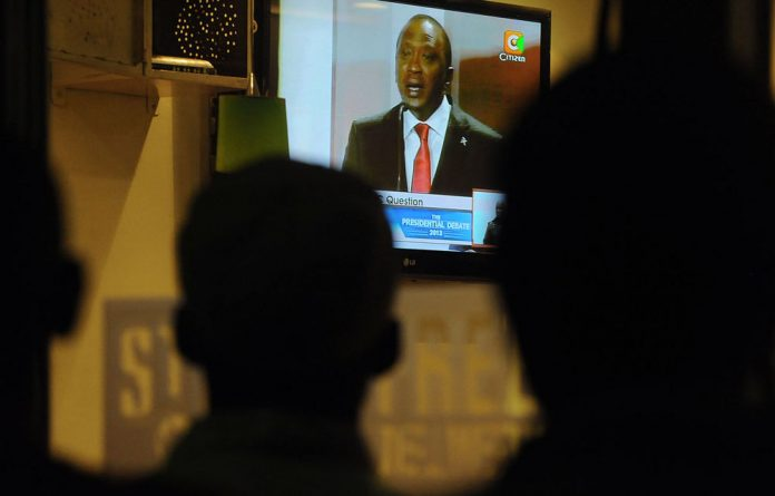 Kenyans watch the National Alliance presidential candidate Uhuru Kenyatta during the first ever face-to-face presidential debate on February 11 2013 in Nairobi.