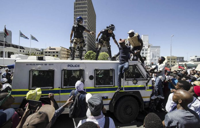 Co-ordinated action: Students are moved off a police nyala after gathering outside Parliament.