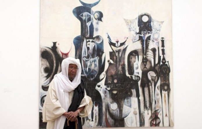 Sudanese artist Ibrahim el-Salahi poses for a photograph in front of his painting entitled 'Reborn Sounds of Childhood Dreams' at the Tate Modern in London.