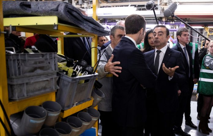 French President Emmanuel Macron discusses with Renault CEO Carlos Ghosn during a visit in the Renault factory in Maubeuge