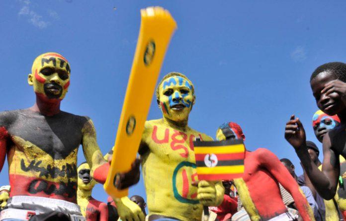 Soccer fans dance outside Mandela National Stadium in the outskirts of Uganda's capital Kampala.