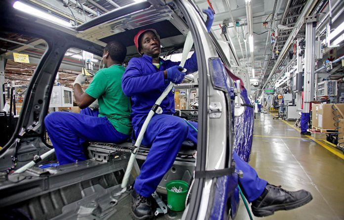 Workers fit electrical system cabling to the interior of a BMW 3 Series automobile as it passes along the production line at the BMW AG plant in Rosslyn.