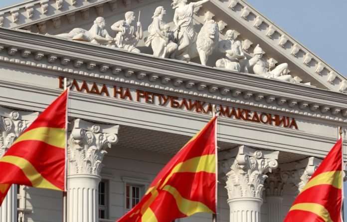 National Macedonian flags flutter in front of the government building in Skopje.