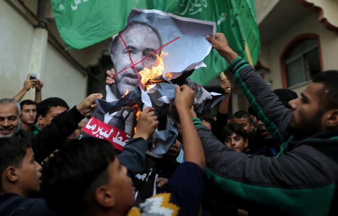 Palestinians burn a poster depicting Israel's Defence Minister Avigdor Lieberman as they celebrate after Lieberman announced his resignation.