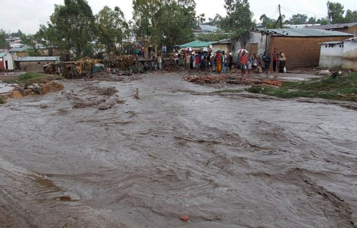 Villagers stand near a flooding street in a township on the outskirts of Malawi's capital