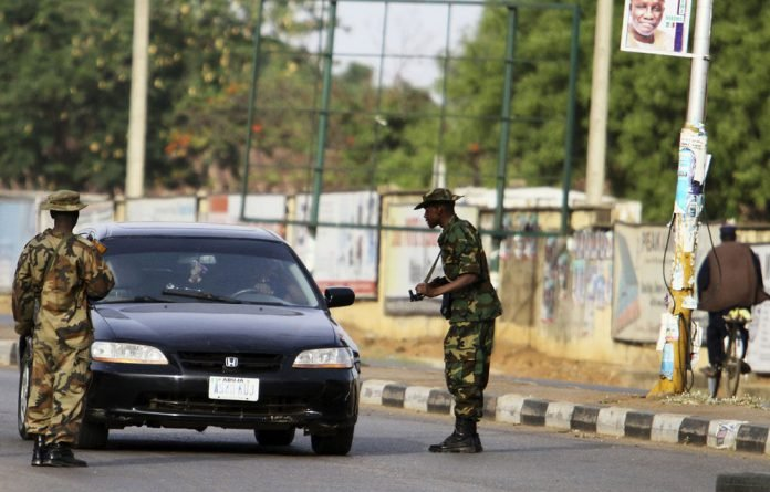 Soldiers stop a vehicle for checks in the Kaduna metropolis in northern Nigeria.