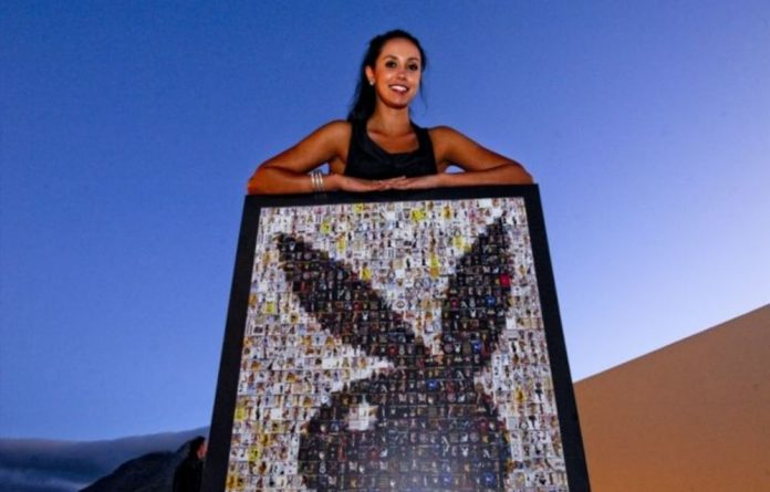 A former playboy model holding a mosaic framed picture of the iconic bunny at the Playboy publishing gala event.