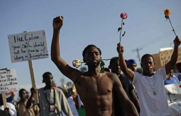 Roses for justice: The fatal shooting of Michael Brown in the United States laid bare the distrust between races.