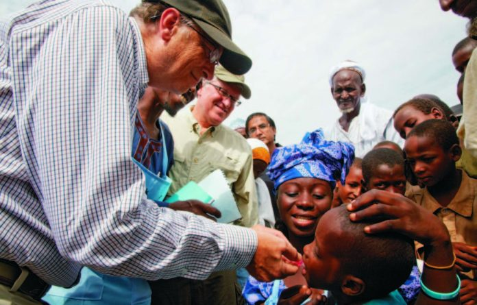 Bill Gates administers polio drops to a child in Nigeria. He spends more on public health than the World Health Organisation's