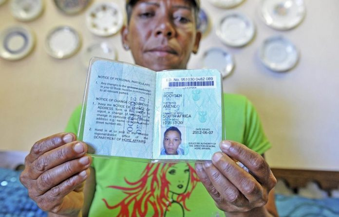 Anene Booysen's foster mother Corlia Olivier holds up her ID book.
