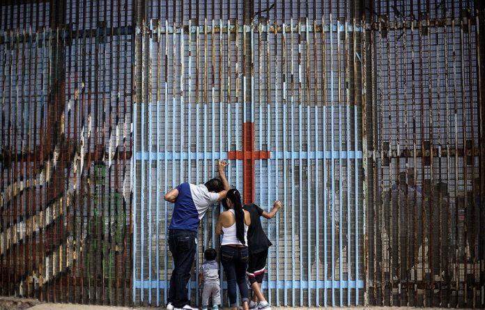A family talks to relatives through the US-Mexico border fence in Playas de Tijuana