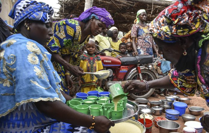 A women's support group meets in Simona village in Yorosso district where they are taught about nutrition such as how to enrich maize meal.