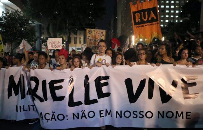 Protesters in Rio de Janeiro walk with a sign reading 'Marielle lives'. EPA/Marcelo Sayao