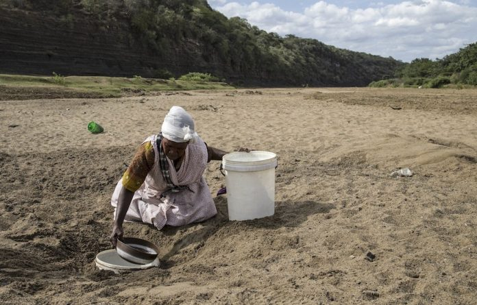 A woman gets water from a well dug in the Black Imfolozi River bed