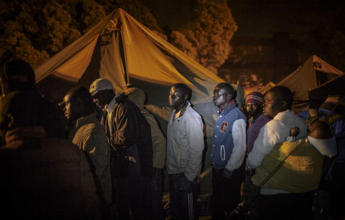On the margins: Residents at a camp for people displaced by xenophobic violence outside Johannesburg in April 2015 wait in line to get a food voucher for dinner.