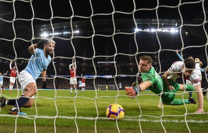 Manchester City striker Sergio Aguero looks on after scoring his hat trick goal despite the efforts of Arsenal goalkeeper Bernd Leno and Laurent Koscielny.