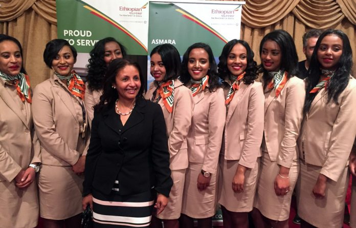 Ethiopian Airlines cabin crew pose for a photograph as they resume flights to Eritrea's capital Asmara at the Bole International Airport in Addis Ababa