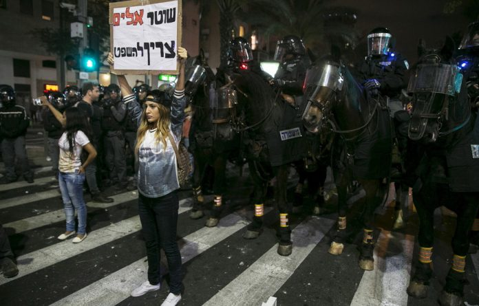 A protester holds a placard in front of a row of policemen on horses during a demonstration against what mainly Israeli Jews of Ethiopian origin say is police racism and brutality.