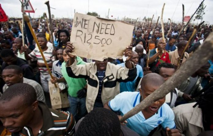 Miners at Marikana protest in 2012. Their poor living conditions were exposed by the Farlam inquiry.