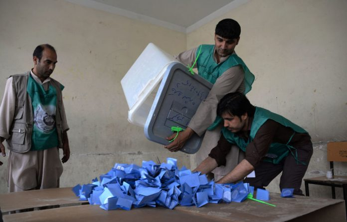Afghan election workers empty a ballot box during the counting process at a polling station in Mazar-i-Sharif.
