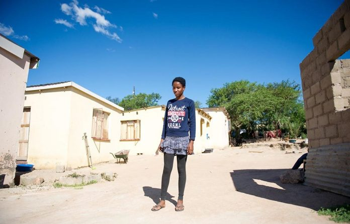 Phiwokwakhe Nxumalo stands in front of her home in Swaziland. She is attending school in South Africa.