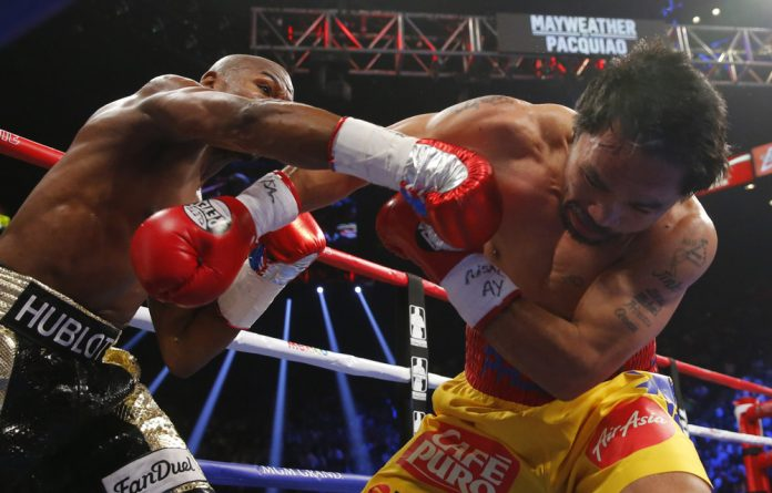 Manny Pacquiao of the Philippines takes a punch from Floyd Mayweather of the US in the second round during their welterweight WBO