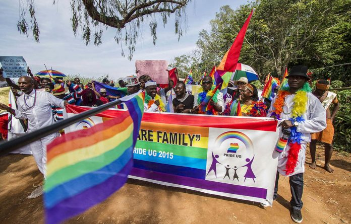 Participants hold rainbow flags during the Gay Pride parade in Entebbe