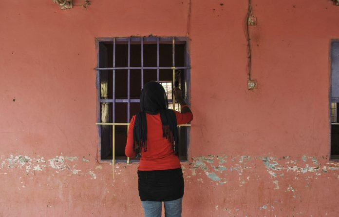Injustice: A woman peers through a courtroom window. The Sudanese authorities