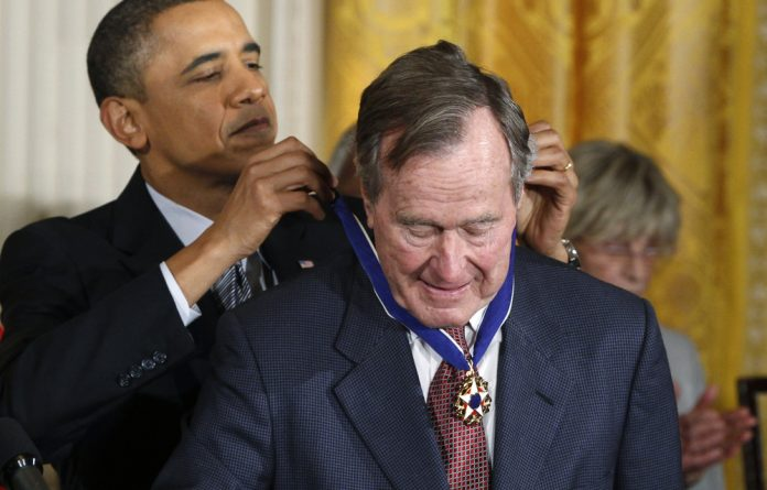 Former US president Barack Obama awards the Medal of Freedom to former US president George H.W. Bush during a ceremony to present the awards at the White House in February 2011.