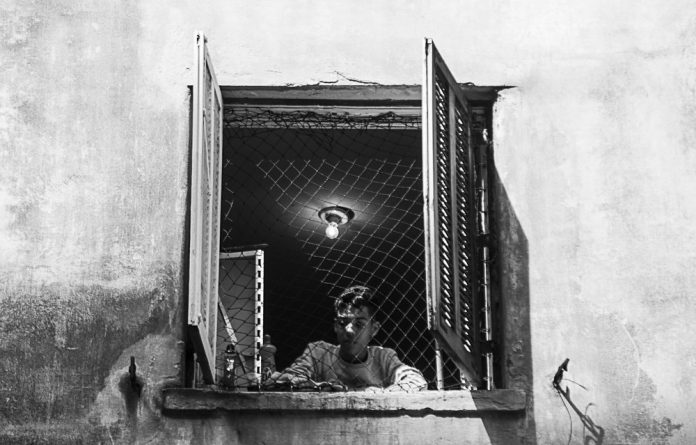 Neighbourhood watch: A boy stares out of the window of an occupied building in Sao Paulo. Social movements have been using loopholes in the Constitution to redress housing backlogs.