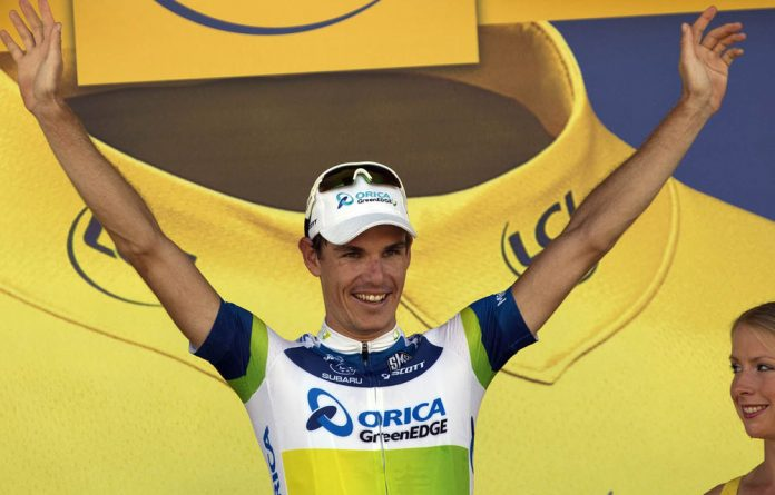 Daryl Impey celebrates his yellow jersey of overall leader on the podium at the end of the 176.5 km sixth stage of the 100th edition of the Tour de France.