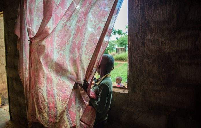 A young boy takes care of his siblings at home in a village in Komatiepoort while his parents are out working.