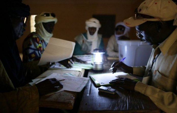 Mali's electoral agents count the votes at a polling station in Kidal