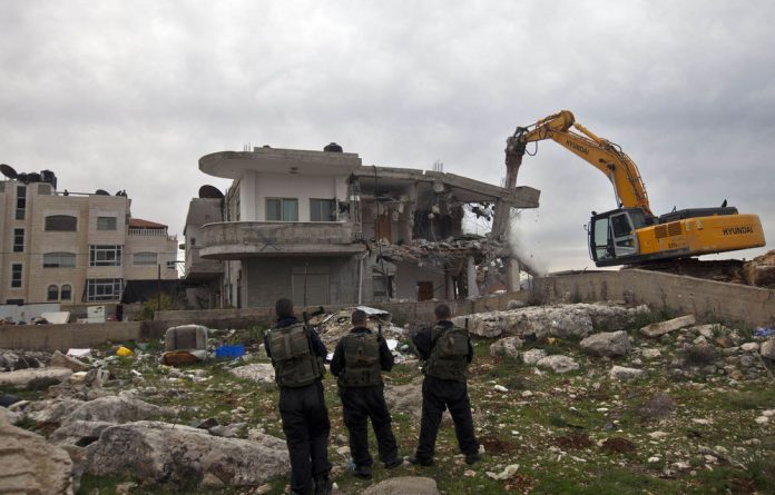 City of conflict: Israeli security officers keep watch as a bulldozer destroys a Palestinian house in the Arab east Jerusalem neighbourhood of Beit Hanina.