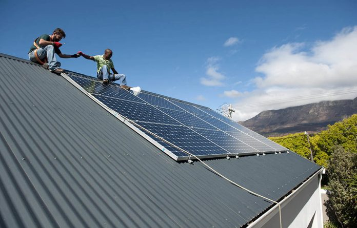 Sunspot Solar Energy Systems employees install solar panels at a private residence in Cape Town.