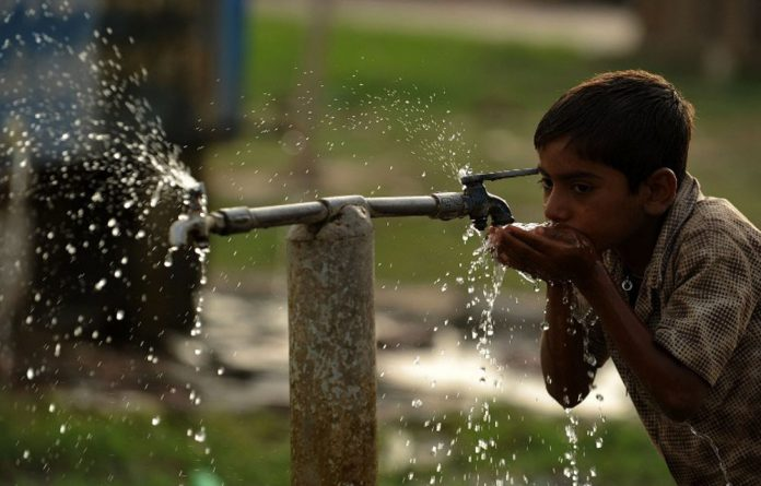 A young boy drinks water from a roadside tap near Sangam in Allahabad
