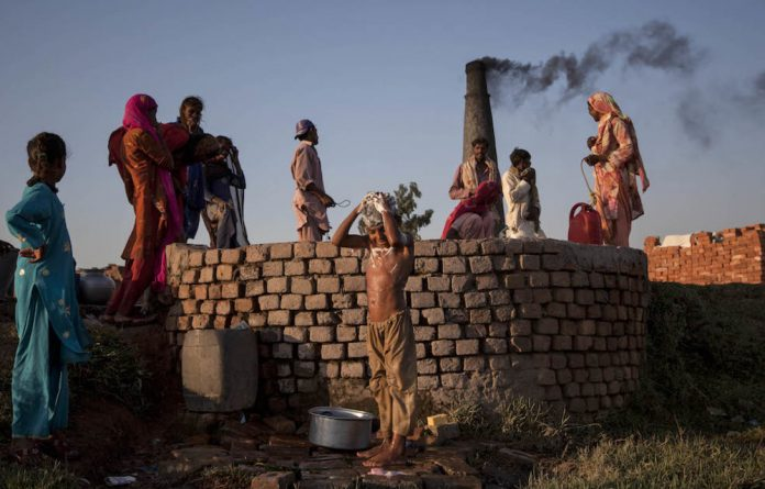 A boy bathes next to a well while his family members collect water at a brick factory on the outskirts of Islamabad