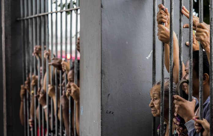 Turf war: Relatives wait for information after prisoners were killed inside a jail in Amazonas