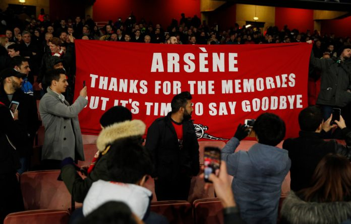 Arsenal fans hold up a banner protesting against Arsenal manager Arsene Wenger after the game against Bayern Munich.