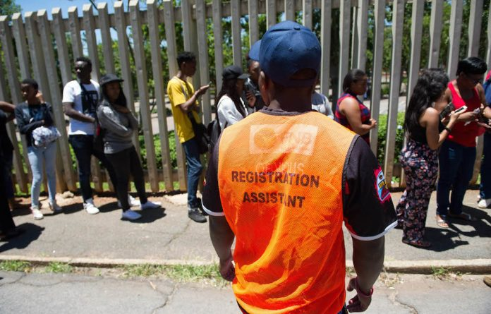 Students at the University of Johannesburg stand in a queue to complete their registration process for the 2017 academic year.