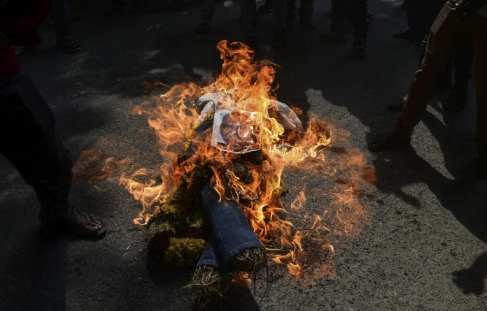 Indian demonstrators burn an effigy of Vedanta Resources boss Anil Agarwal because of the killings of at least 10 people during a protest about pollution from a copper factory.