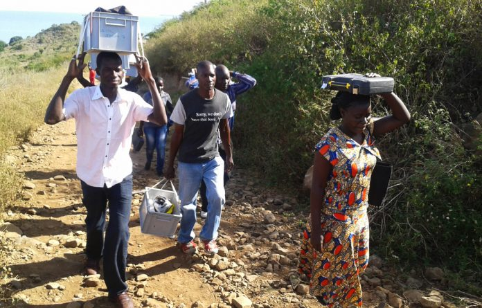 A research team installs novel solar-powered mosquito traps on rural Rusinga Island in Western Kenya.