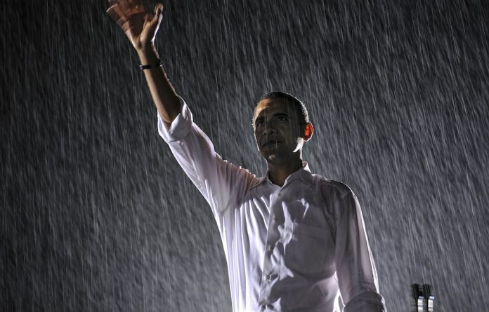 Barack Obama waves as rain falls during a rally for his first presidential term