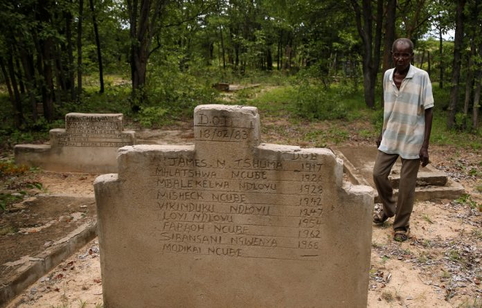A man walks past graves of people killed during the massacre.