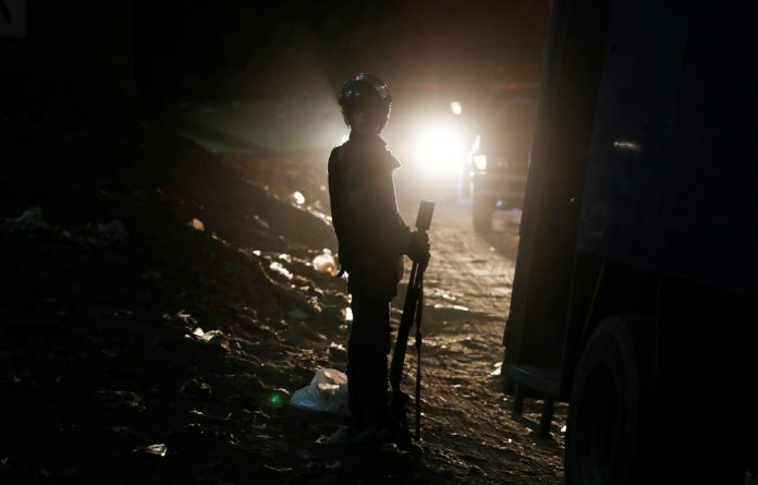 A riot policeman secures a scene of a bus blast in Giza