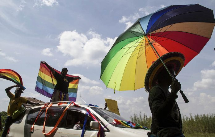 Participants in a gay pride rally in Uganda in 2014 sport rainbow flags and an umbrella in the same colours.