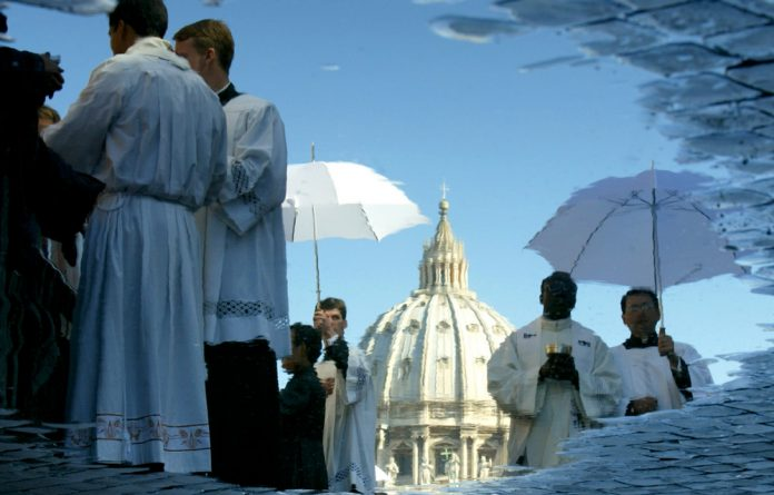 A puddle reflects St Peter's Basilica and priests as they give holy communion during a beatification ceremony of Mother Teresa.