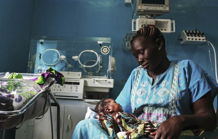 A woman holds her newborn baby in a nursery at the Juba Teaching Hospital. Very few births in South Sudan